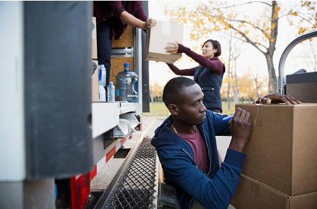 personnes chargeant et déchargeant des cartons dans un camion de déménagement